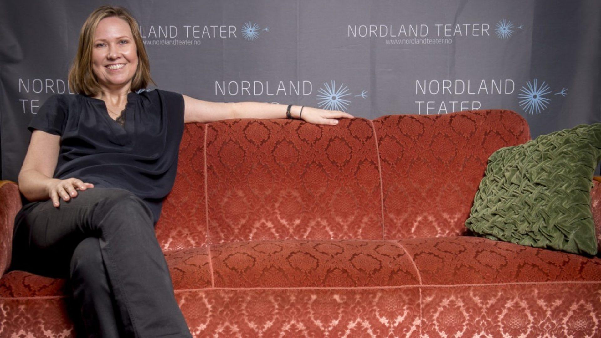 Birgitte Strid sitter i en sofa