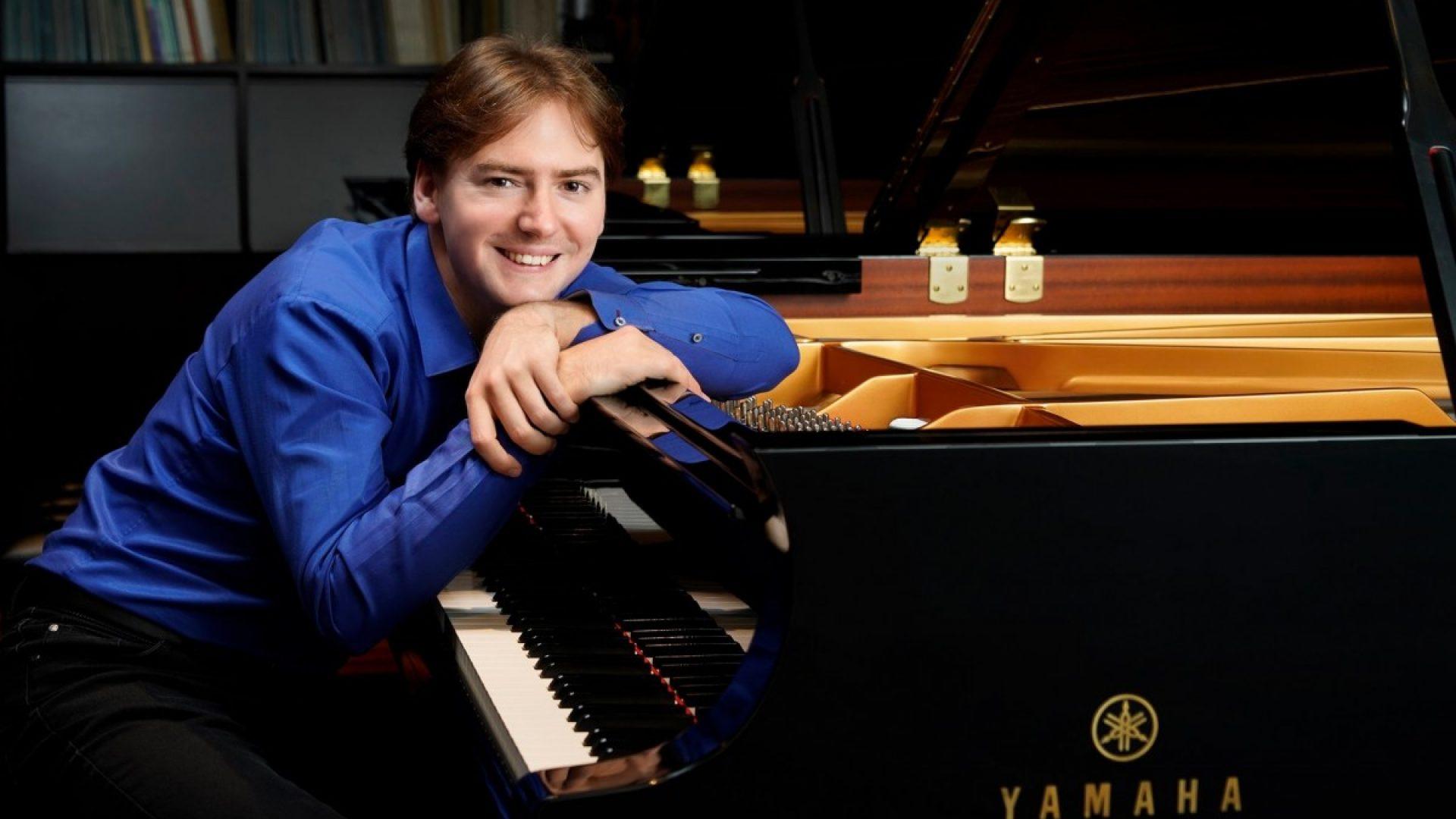 Bilde av unggutten Gregor, lenende på et utsøkt Yamaha-piano. Han har på seg penskjorte som man hør og bør når man skal fremføre klassiske pianoverk fra Chopin.