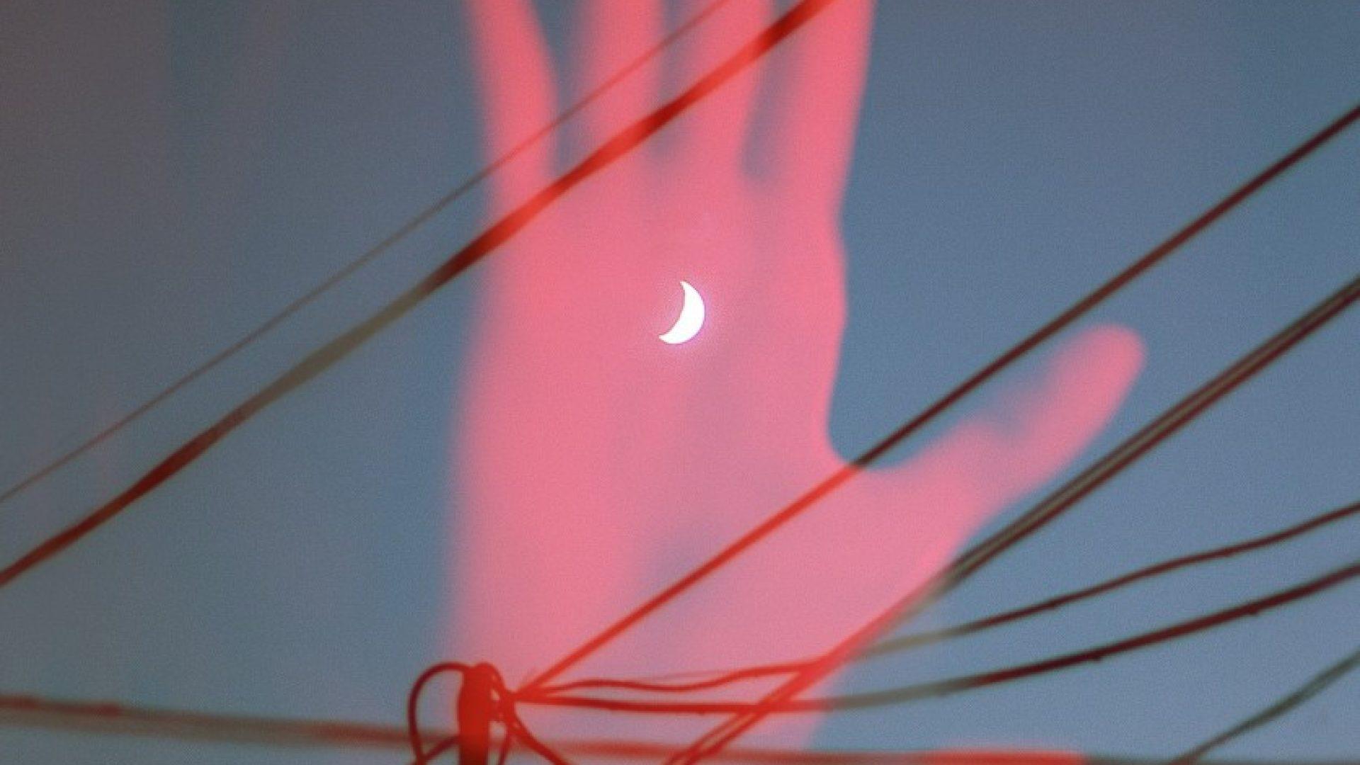 En rød hånd blant strømledninger. Månen skinner gjennom hånden.