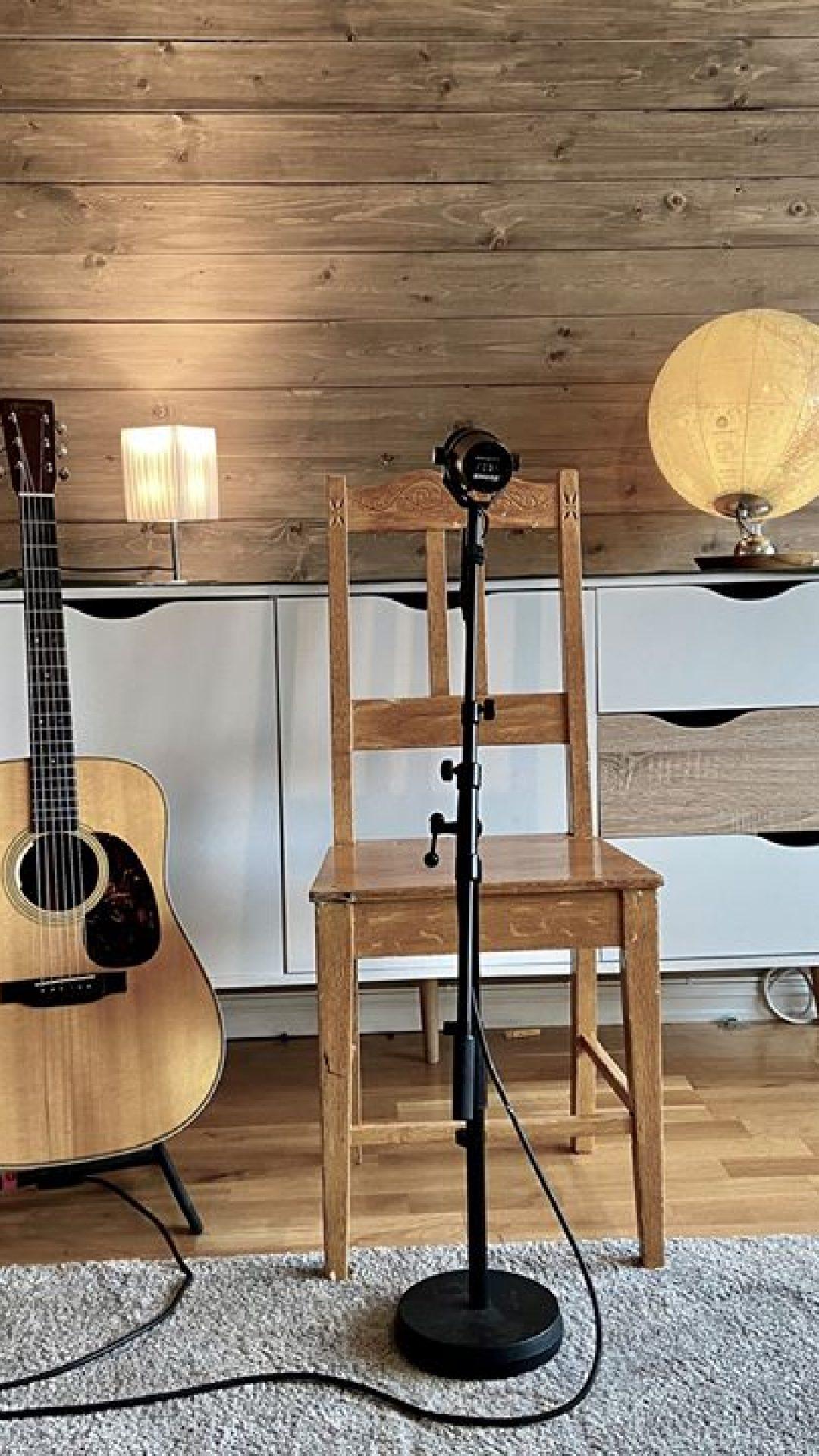 Hjemmescene med stol, gitar og mikrofon
