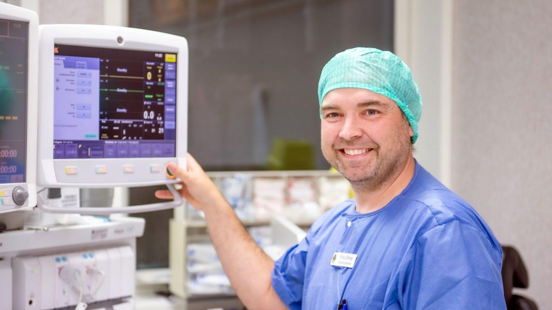 Medisinsk personell med blå klær på. Bredt smil.