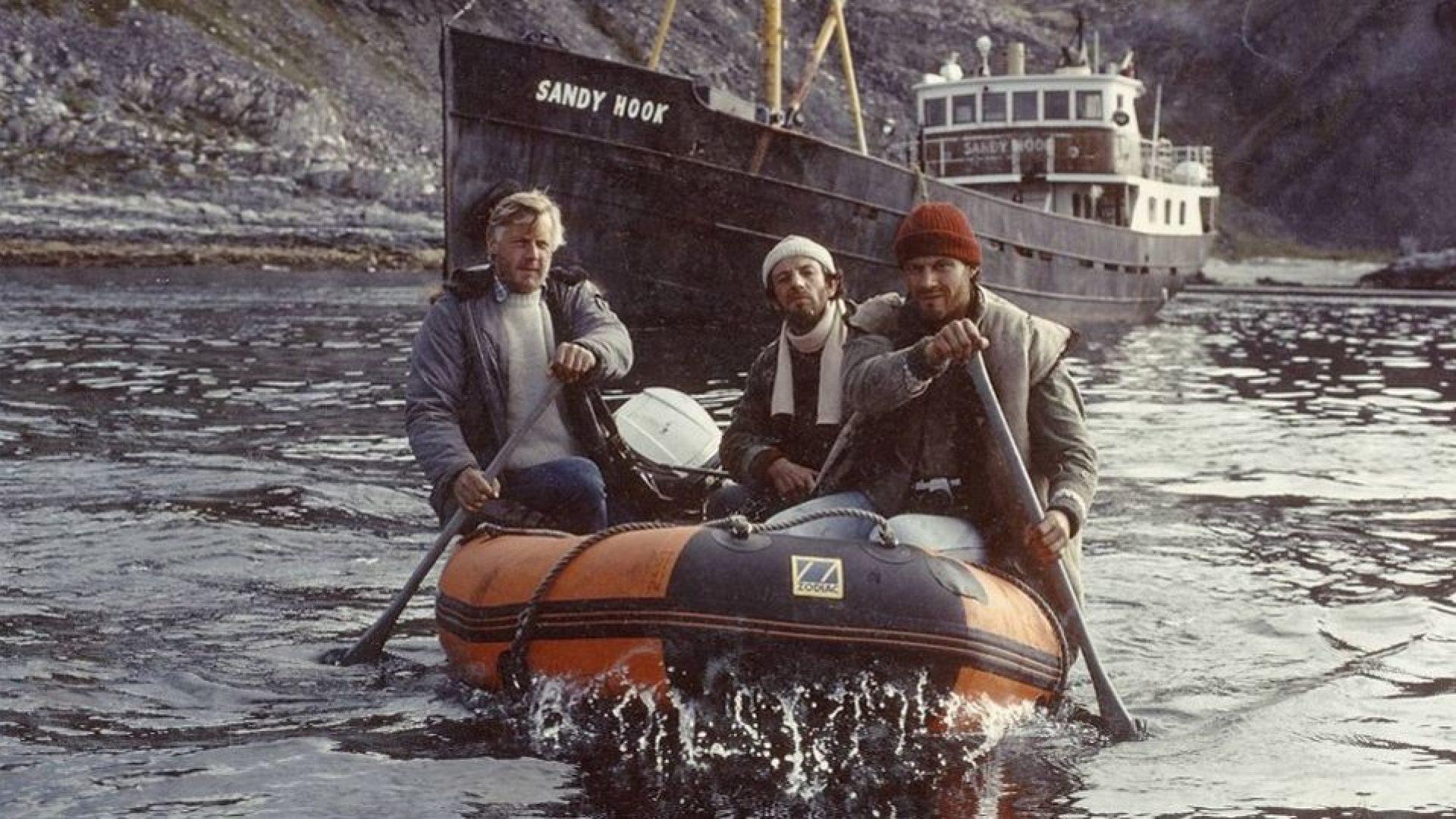 Tre menn i gummibåt, i bakgrunnen ser vi skipet Sandy Hook