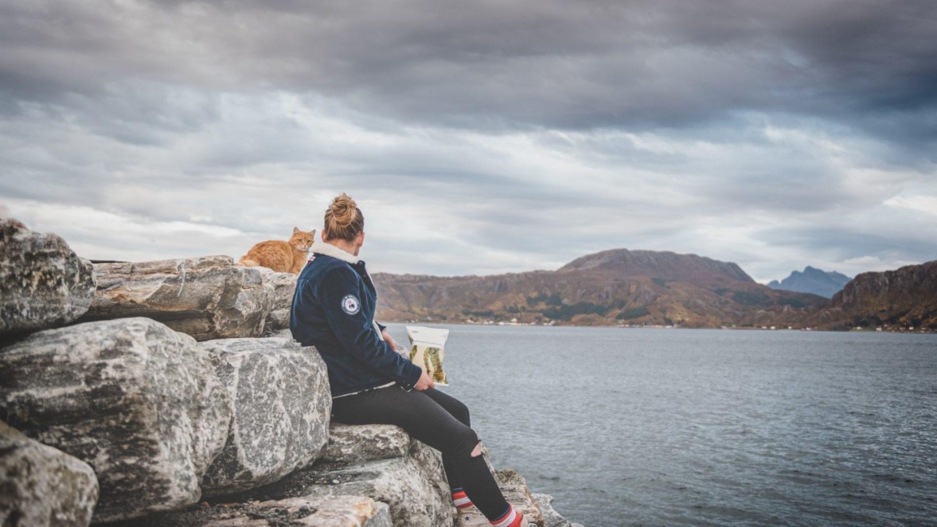 Dame som holder en pose med SjySnack ser ut over fjorden