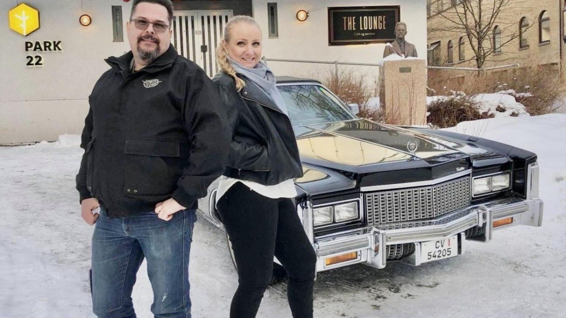 Par poserer ved amerikansk bil